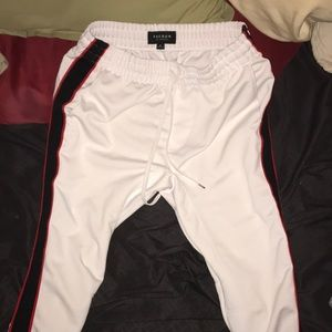 White joggers with red and black stripes on side